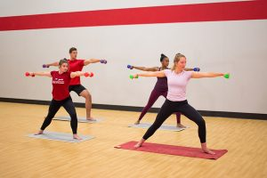 Photo of four fitness instructors performing a lunge with their arms outstretched to their sides in-sync