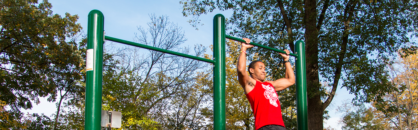 Photo of a man doing pull-ups on fitness trail equipment outdoors