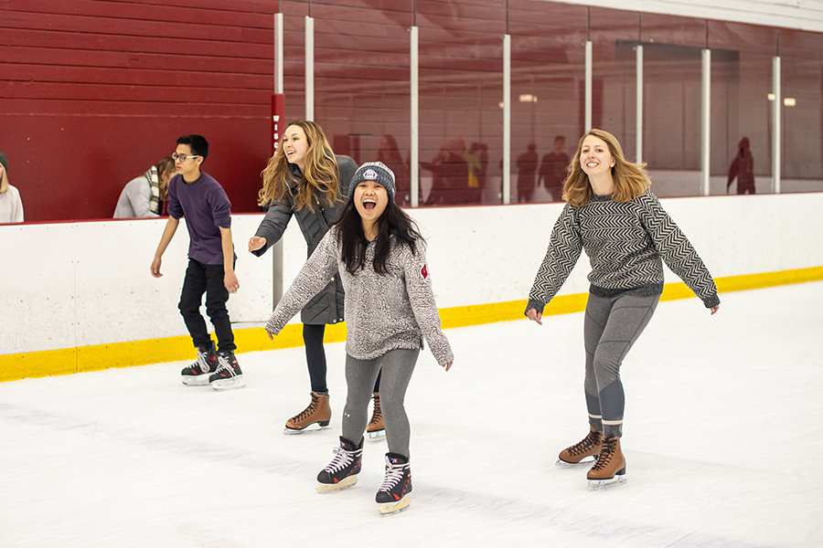Photo of four students smiling and figure skating in-sync on an indoor ice rink at the Shell