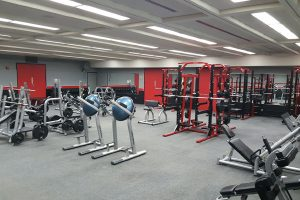 Photo of an indoor weight room equipped with squat racks, workout machines, and free weights