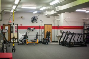 Photo of an indoor fitness studio equipped with a bench press, TRX equipment, and free weights