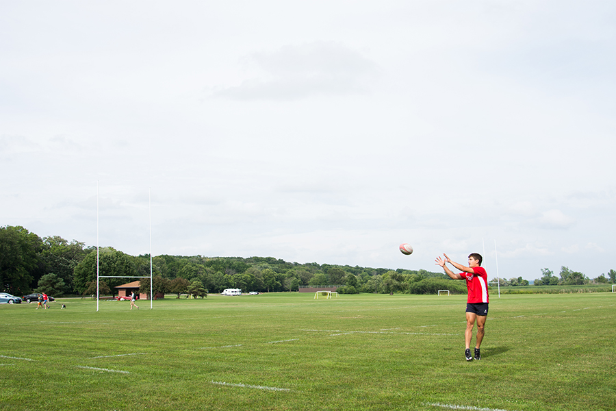 Photo of a man catching a football outdoors on the University Bay Fields