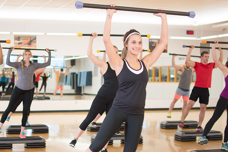 Photo of a group of fitness instructors raising a barbell above their head in-sync during an indoor fitness class