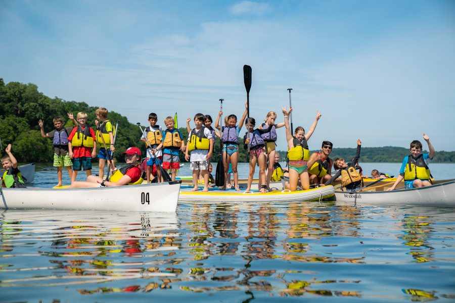 Photo of a group of children standing on paddle boards and canoes on Lake Mendota with their hands up in the air as they all wear matching yellow lifejackets