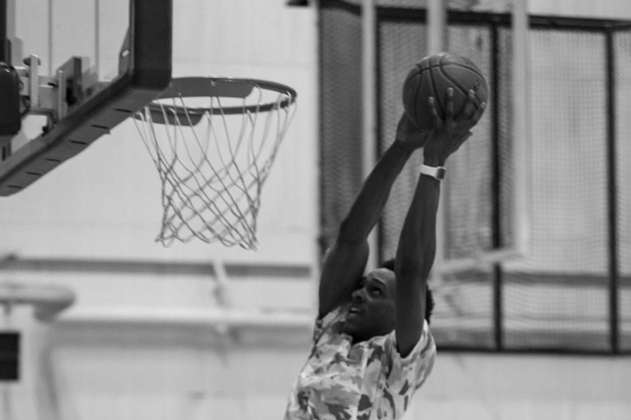 black and white photo of a basketball player dunking the ball during intramural sports