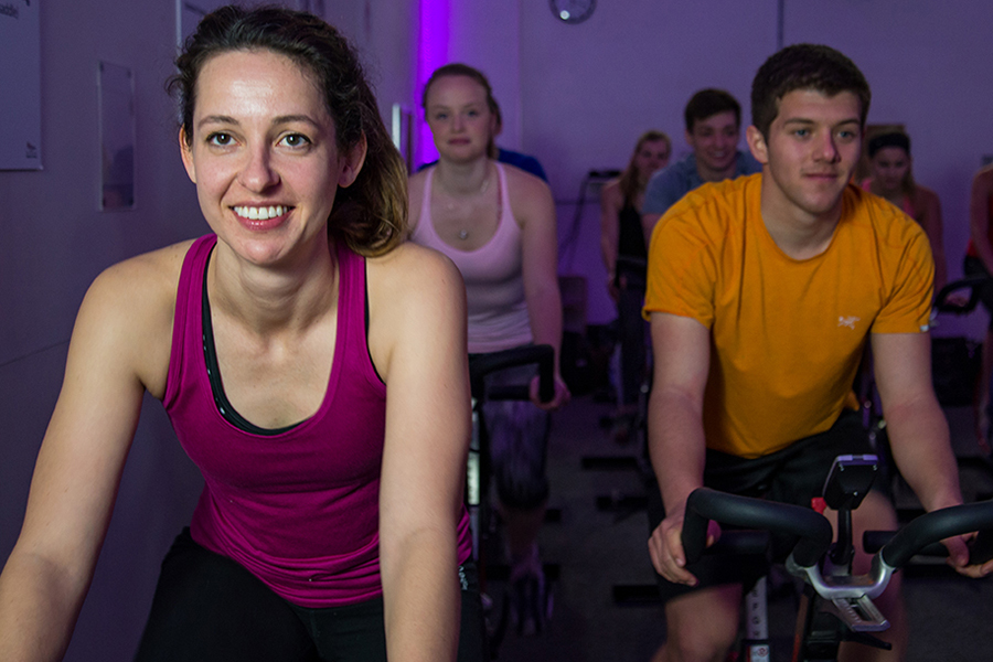 Photo of people smiling as they cycle during an indoor cycling group fitness class