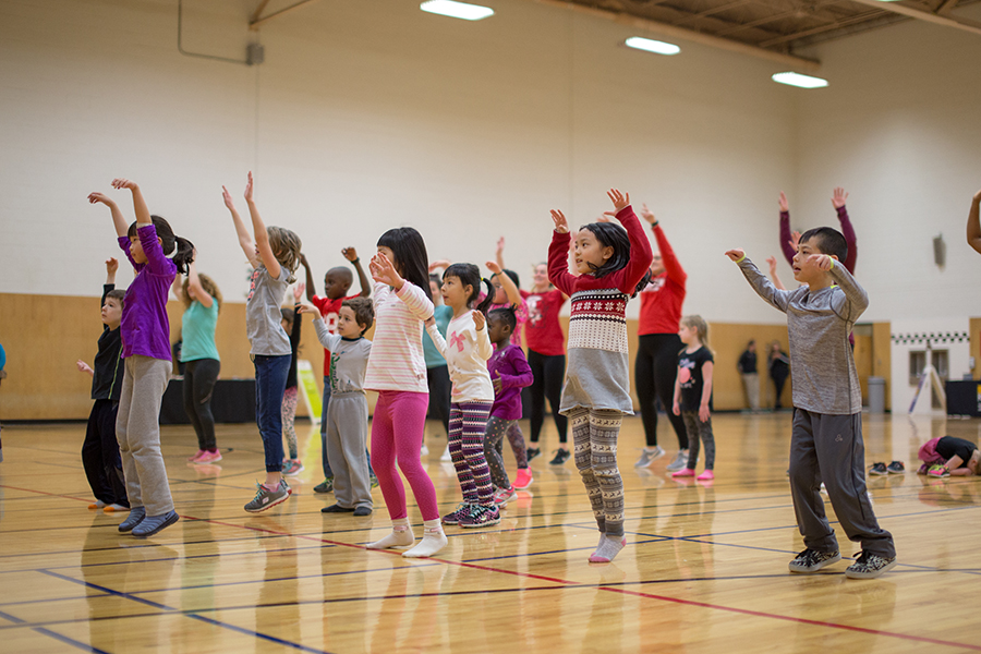 Photo of a group of children jumping with their hands above their heads in an indoor gym