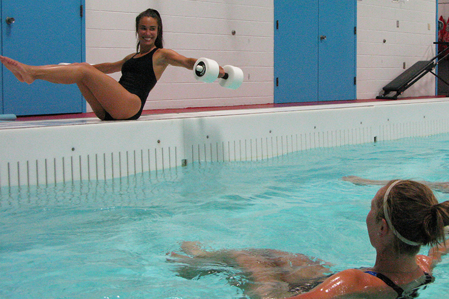 Photo of a fitness instructor on the side of the pool leading participatns in a workout as they float in the pool beside her