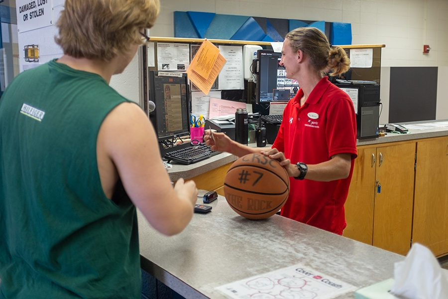 Photo of a staff member checking out a basketball to a fitness club member