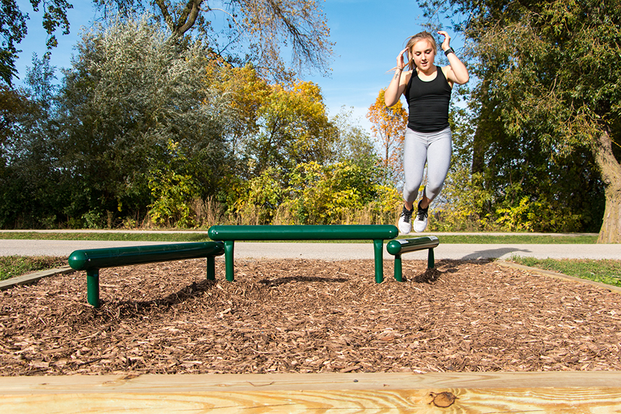 Photo of a woman jumping over a beam outdoors on the fitness trail