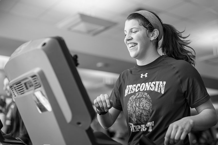 black and white image of female participant smiling as she runs on a treadmill