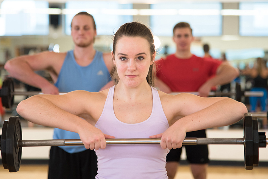 Photo of a women raising a barbell with both hands in front of her chest during a group fitness class