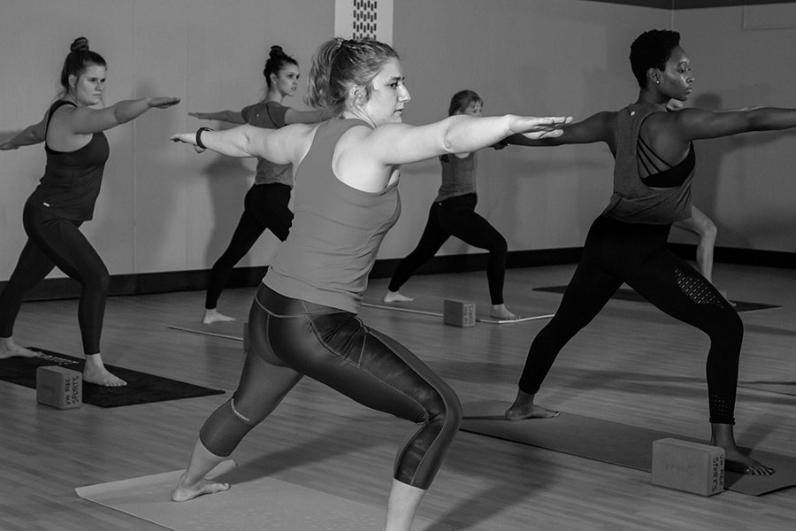 Black and white photo of a group of participants performing the warrior yoga pose during a group fitness class