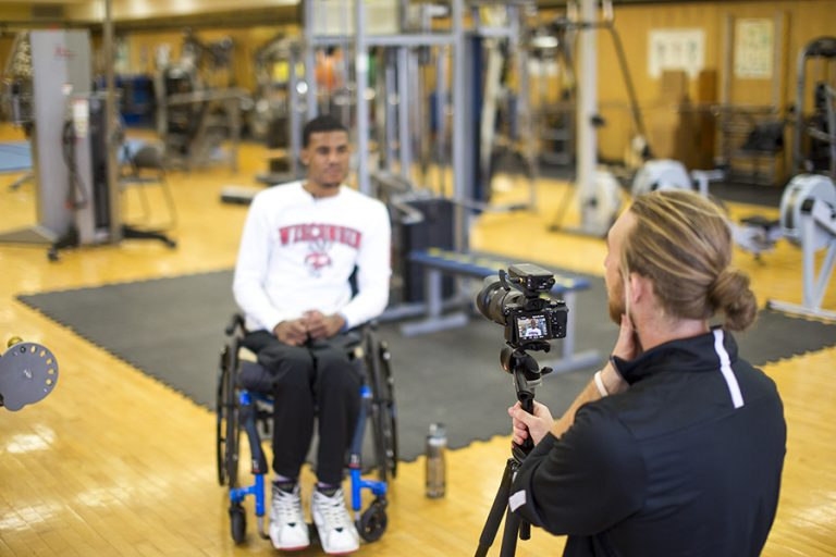 Photo of a man in a wheelchair having his photo taken in an indoor gym