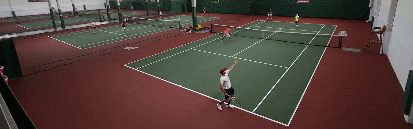 Photo of a man serving a tennis ball at the Nielsen Tennis Stadium courts