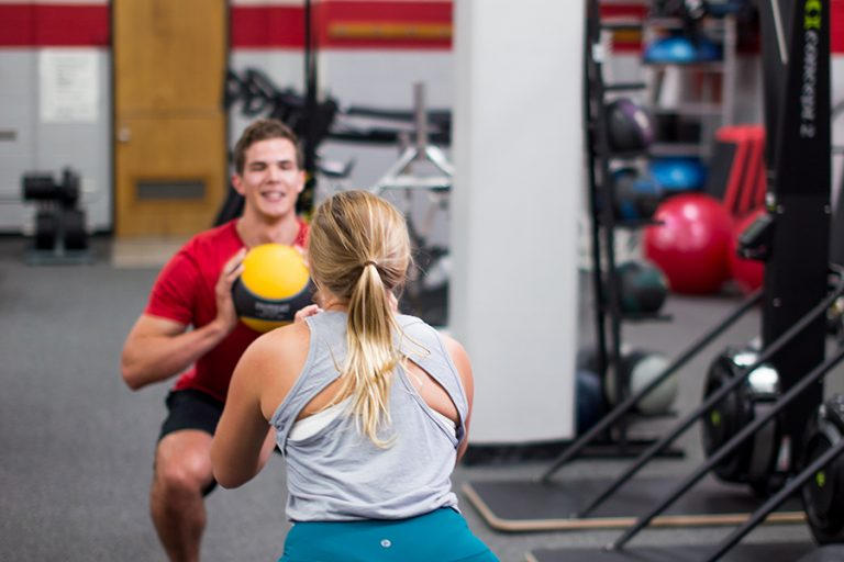 Photo of a man and a woman facing each other and squatting as they pass a medicine ball back and forth in an indoor weight room