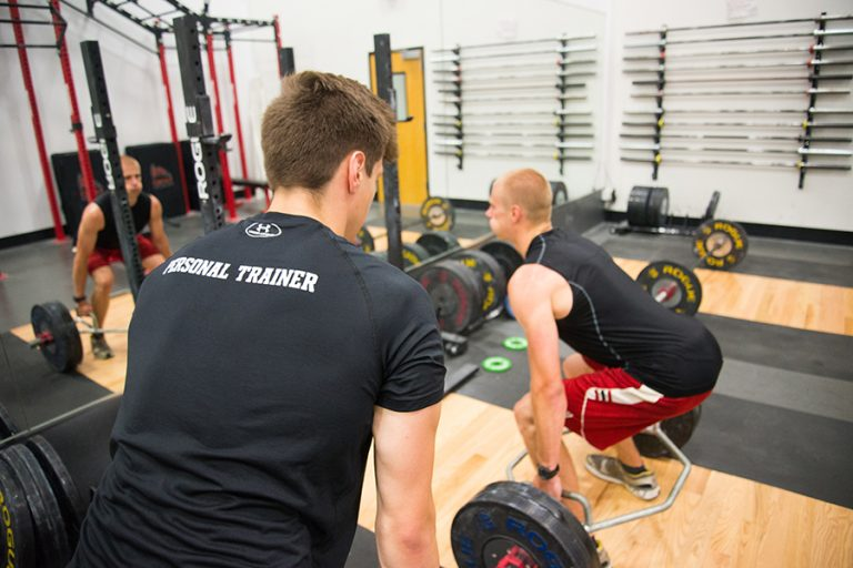 Photo of a personal trainer standing beside a man as he stands in a squat position in an indoor weight room