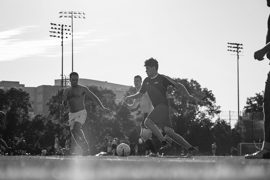 black and white photo of three male participants playing soccer on near west fields