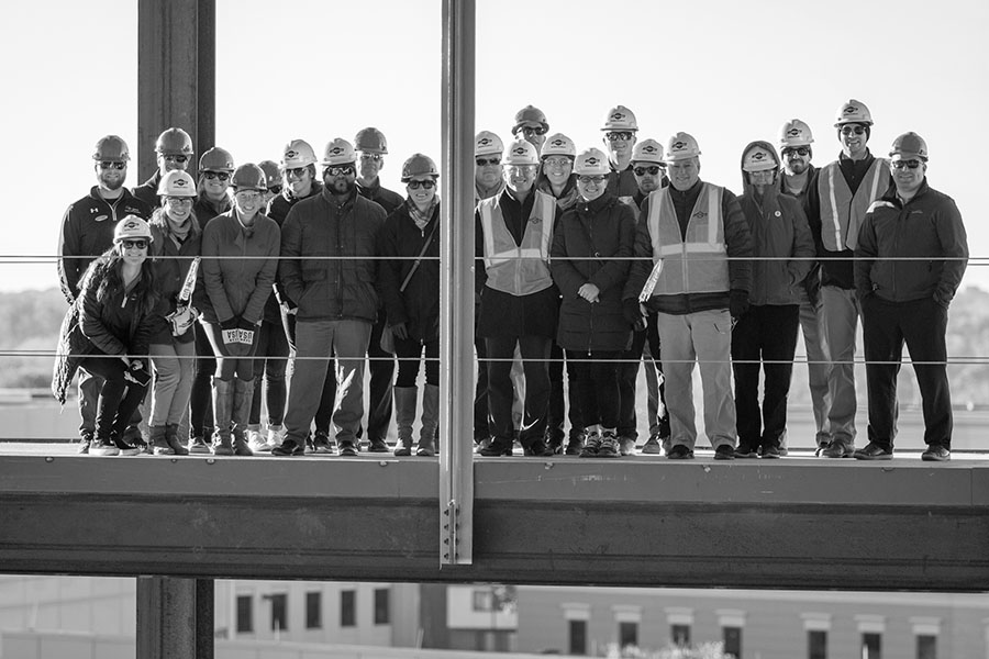 Black and white photo of a Rec Well professional team standing on the track of the new Nicholas Recreation Center during construction