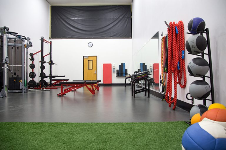Photo of an indoor fitness center equipped with benches, medicine balls, resistance bands, and ropes
