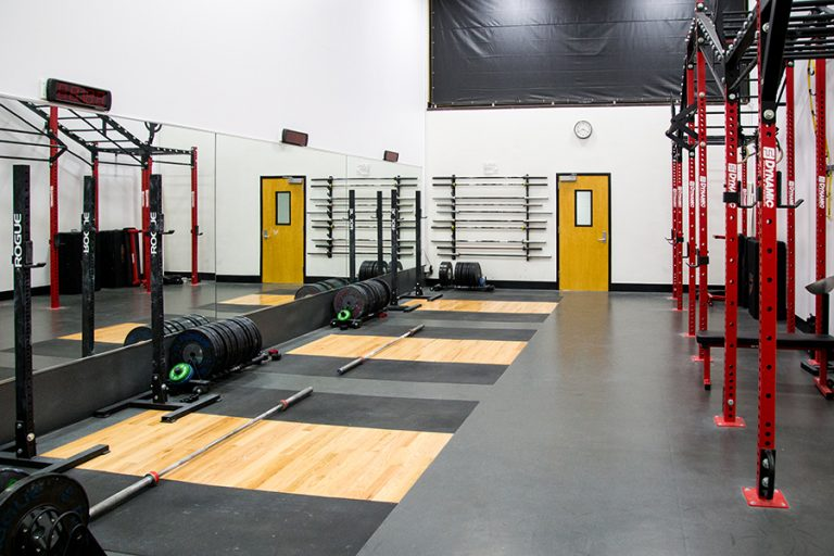 Photo of an indoor weight room equipped with squat racks, barbells, and plates