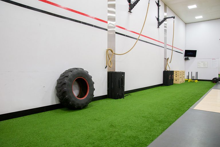 Photo of a turf strip in an indoor fitness center with a tire and ropes for exercising