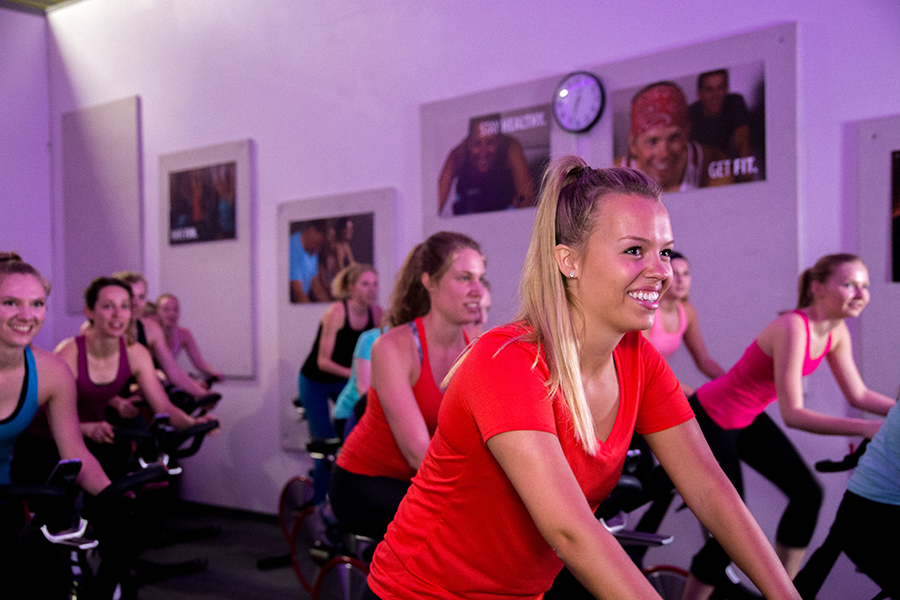 Photo of a group of women smiling and sitting on bikes during an indoor cycling group fitness class