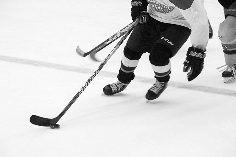 Black and white photo of a hockey player skating on the ice with a puck near his hockey stick