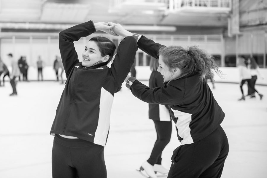 Black and white photo of two female ice skaters twirling each other as they skate on an indoor rink