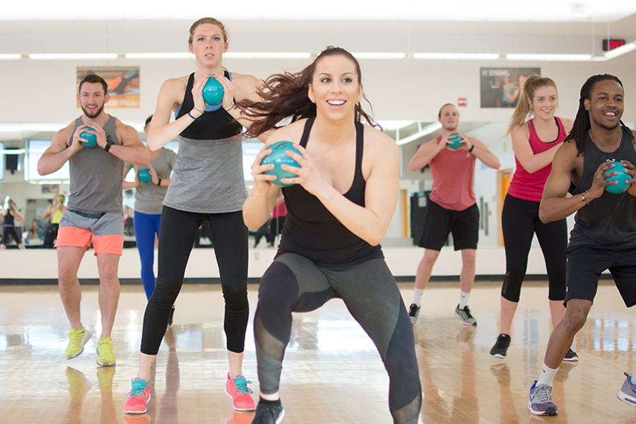 Photo of a group of fitness instructors jumping and holding a ball during an indoor group fitness class