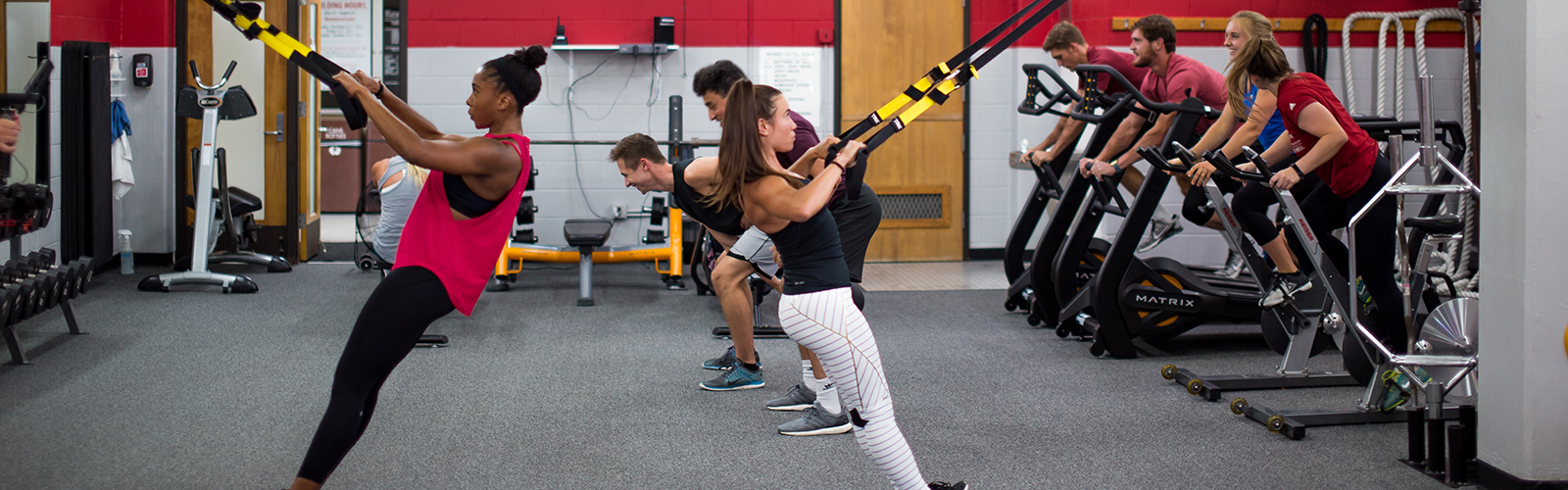 Photo of a group of people performing various TRX and cardio exercises in an indoor weight room