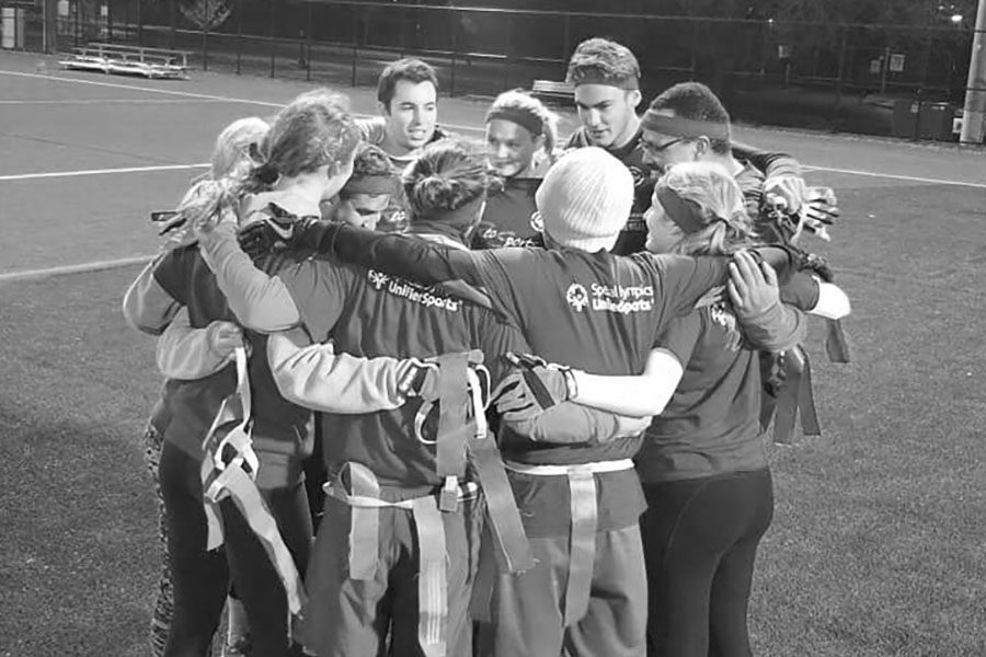 black and white photo of unified team in huddle