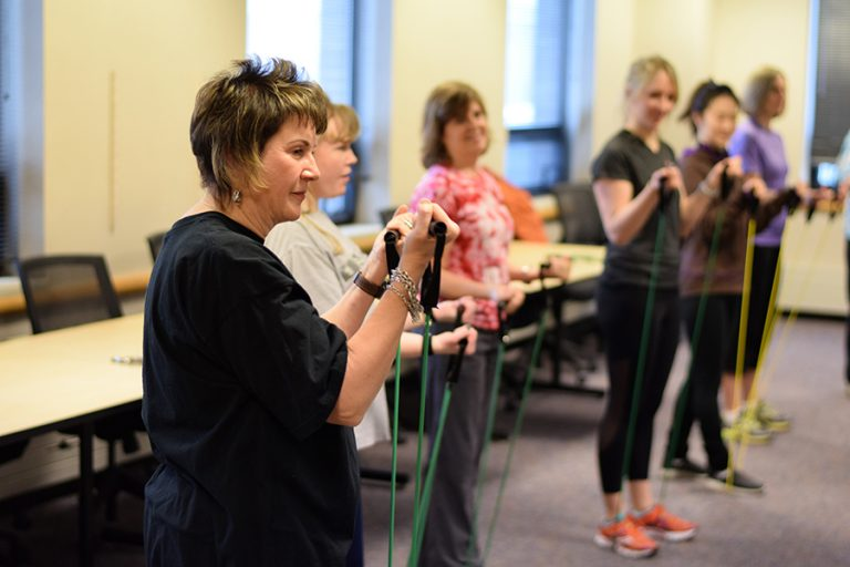 Photo of a group of middle-aged women gripping resistance bands during in indoor workout class