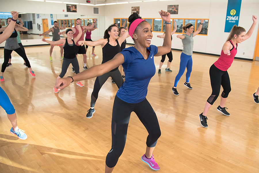 Photo of a group of fitness instructors performing a dance move in sync with their arm above their head during an indoor Zumba class