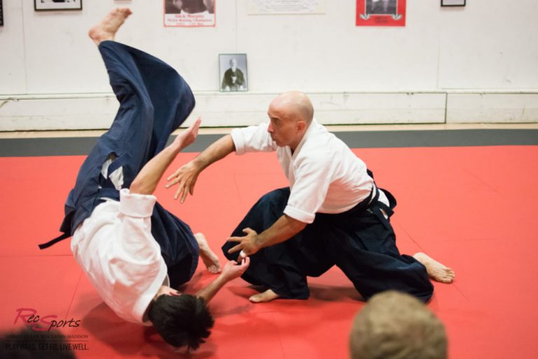 Photo of two men tumbling during an Aikijujitsu match on an indoor arena