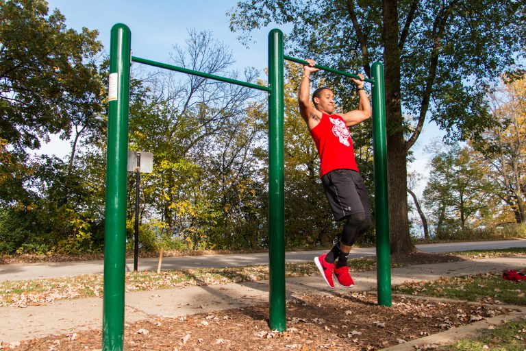 Photo of a man performing a pull-up on an outdoor bar along the Lakeshore Path