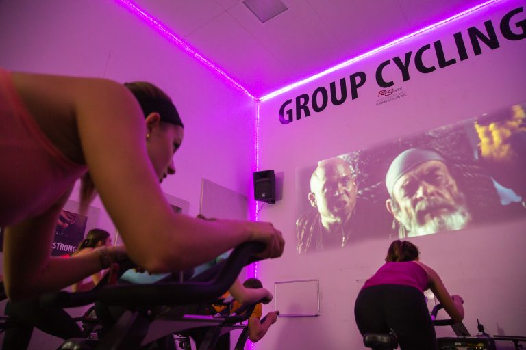 Photo of a group of cyclers watching a movie on a projector during a group cycling fitness class