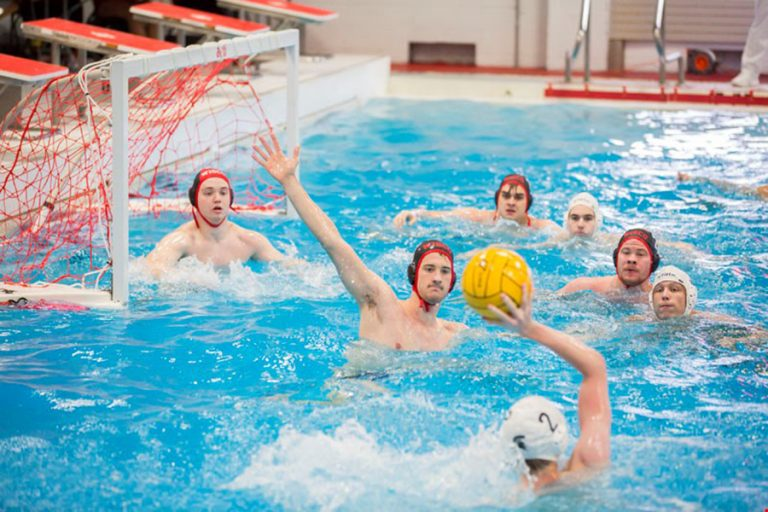 Photo of the UW men's water polo team approaching the goal in the pool during a match