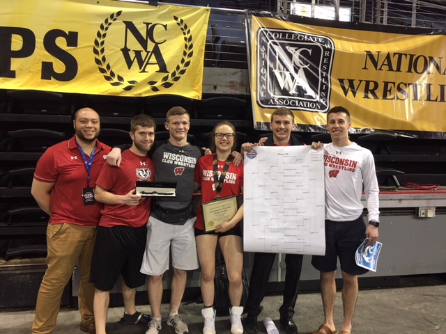 Photo of the UW Wrestling team standing in a row holding up a bracket and certificate at Nationals