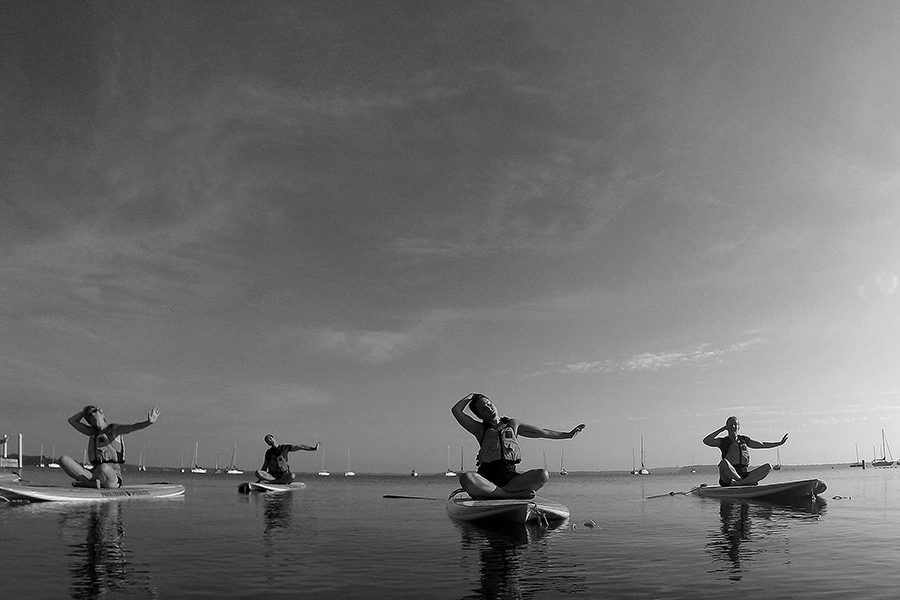 Black and white photo of four people sitting cross-legged on paddle boards with one arm outstretched in unison as they float on Lake Mendota