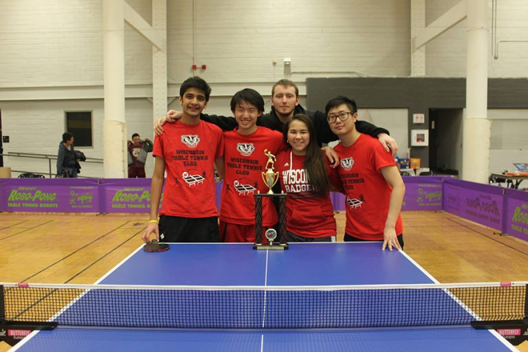 Photo of the UW Table Tennis Club standing together with a large trophy positioned on a table in front of them