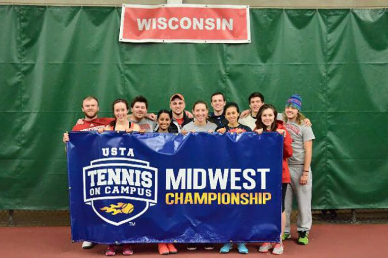 Photo of the UW Tennis Club standing with a Midwest Championship banner