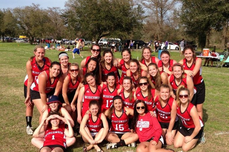 Photo of the UW Women's Lacrosse team standing together in matching uniforms on an outdoor field