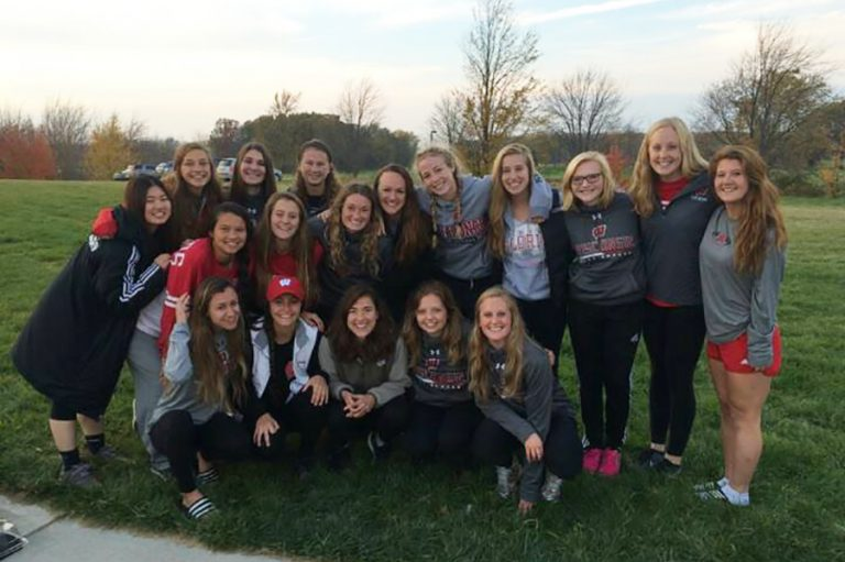 Photo of the UW Women's Soccer team standing together on an outdoor field