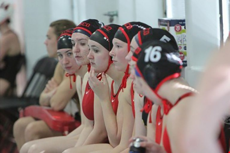 Photo of the UW women's water polo team sitting in a row near the pool