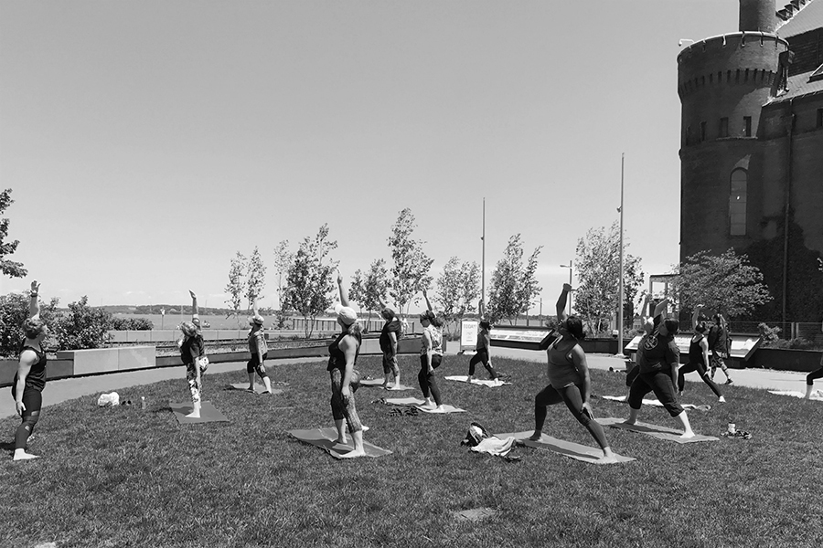Black and white photo of a group of women performing a yoga pose in unison outside on the grass near Lake Mendota