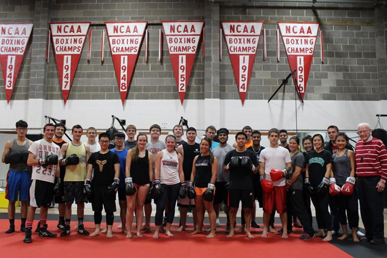 Photo of the UW Boxing team standing together wearing boxing gloves in an indoor gym