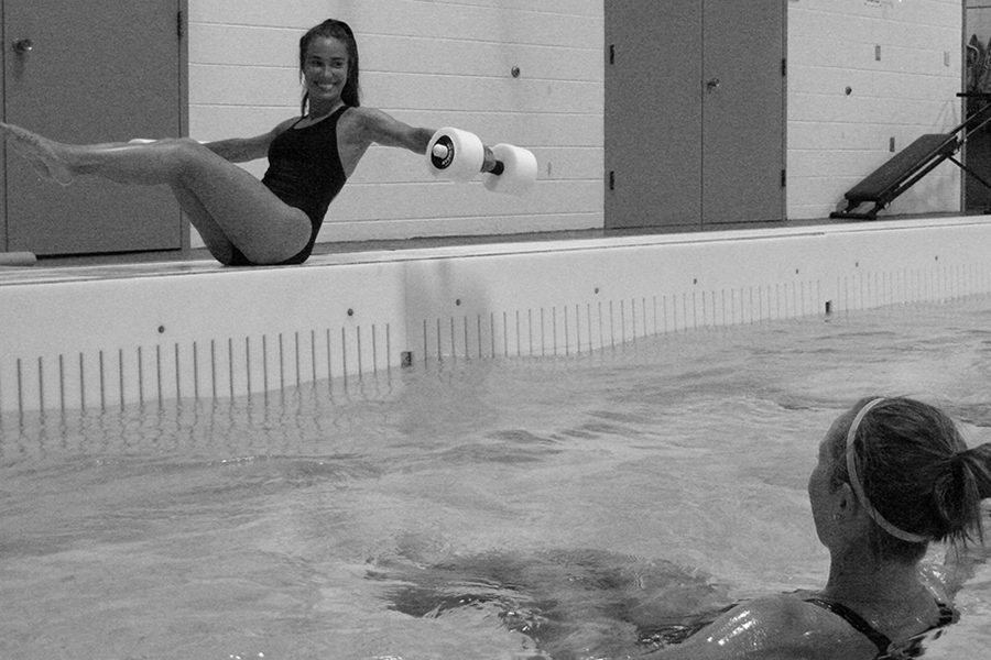 Black and white photo of a fitness instructor sitting beside an indoor pool and leading participants in an exercise with a floating dumbbell