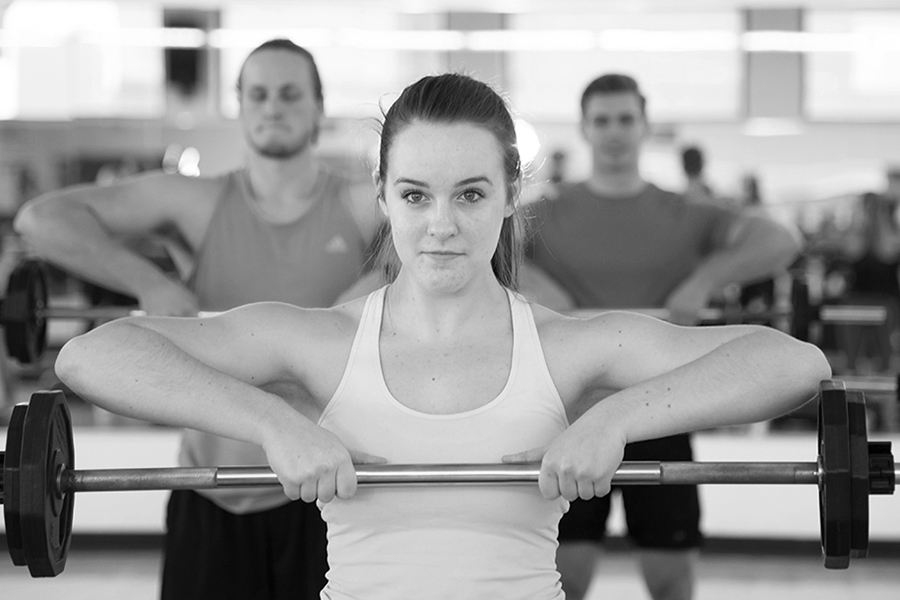 Black and white photo of a woman holding a barbell up to her chest with both hands during an indoor group fitness class
