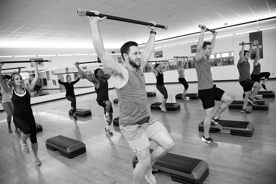 Black and white photo of a group of participants jogging and holding a barbell above their head during an indoor group fitness class